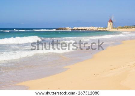 Old windmill on sea coast landscape - stock photo
