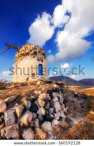 Old windmill ruins on a hill in Santorini island, Greece - stock photo