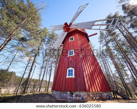 Old windmill surrounded by trees in Finland on a sunny summer day.