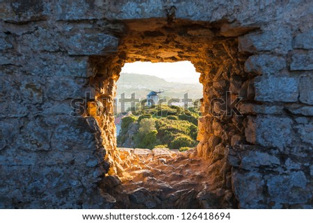 Old Windmill through Small Window in Obidos Fortress Wall, Portugal. Evening Sunlight - stock photo
