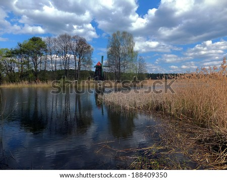 old windmill was built as a tourist attraction built on the island of a small lake in the village Zielona in Poland  - stock photo