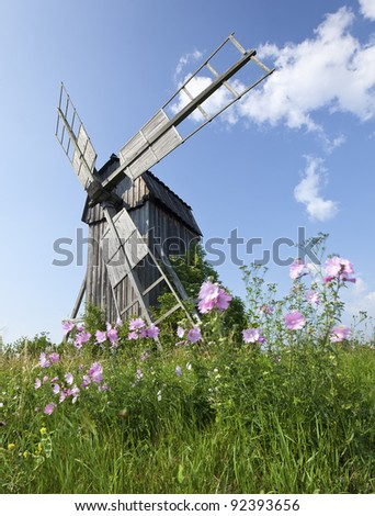 Old windmill with windblown flowers in the foreground
