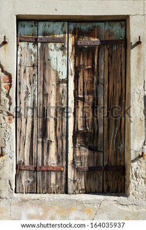 old window closed with wooden shutters in Venice, Italy.