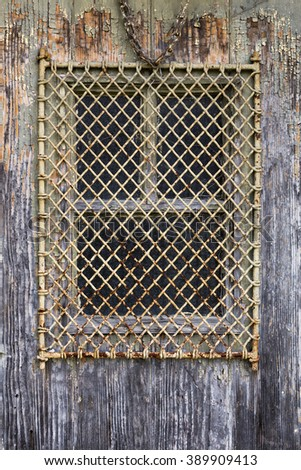 old window covered with a metal grate set in a wood wall