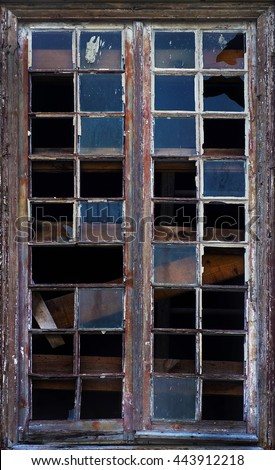 Old window frame with shattered glass in a ruined house - stock photo