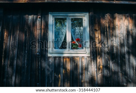 old window in a black classic rustic wooden house