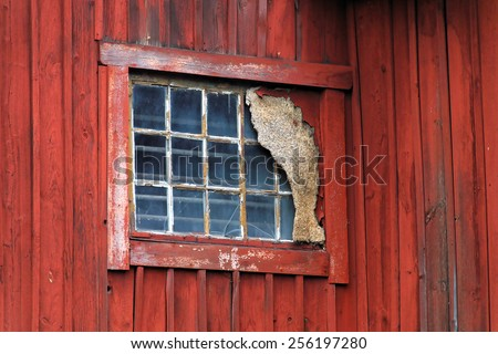 Old window in a red barn wall - stock photo