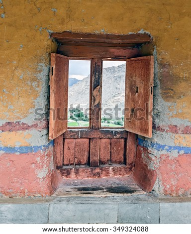 Old window on ritual pole with flags in Likir Gompa (monastery) - Tibet, Leh district, Ladakh, Himalayas, Jammu and Kashmir, Northern India - stock photo