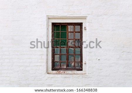 old window with iron grating, brick wall - stock photo