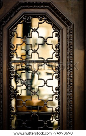 Old window with reflection and steel cage - stock photo