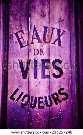 "Old wine and spirit cellar sign. Text in French ""Eaux de vies, liqueurs"" meaning ""Brandy, liqueurs"". Toned photo. - stock photo"