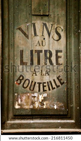 "Old wine and spirit cellar sign. Text in French ""Vins au litre, a la bouteille"" meaning ""Wine selling by liters or in bottles"". Toned photo."