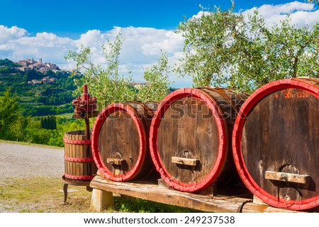 Old wine barrels and squeezer at the entrance of vine and oil stock. Sienna, Tuscany, Italy - stock photo