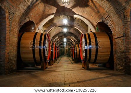 Old wine barrels in the vault of winery - stock photo