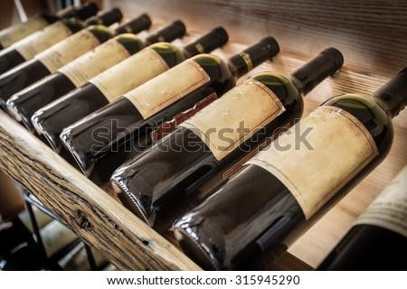 Old wine bottles on the wine shelf. - stock photo