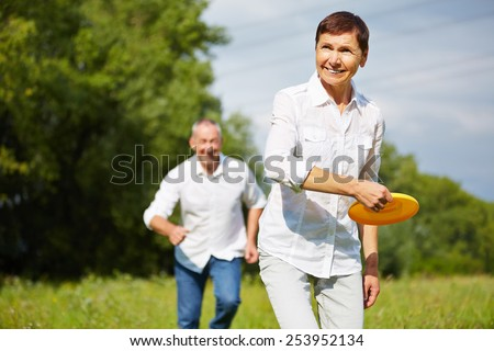 Old woman and man playing frisbee together in summer in nature - stock photo