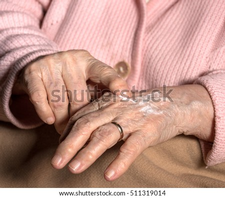 Old woman applying hand cream at home. Close-up of wrinkled woman's hands