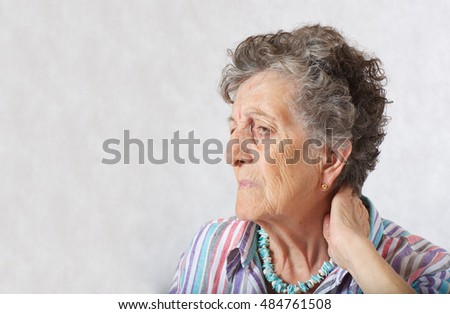 Old woman between 70 and 80 years old suffers from a pain in the neck