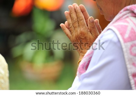 Old woman bring both hands together in obeisance to pay monk - stock photo