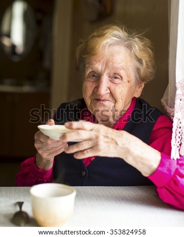Old woman drinking tea in the kitchen. - stock photo