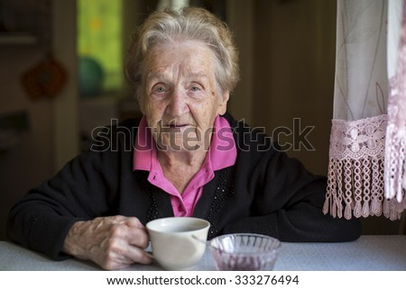 Old woman drinking tea sitting in the kitchen.