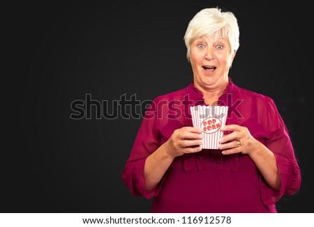 Old Woman Eat Popcorn On Black Background - stock photo