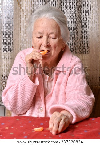 Old woman eating tangerine at home