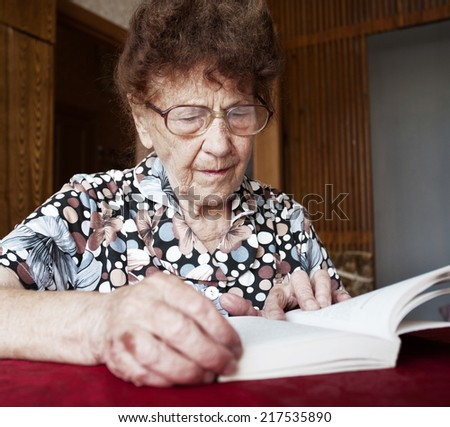 Old woman. Elderly female at home reading Book - stock photo
