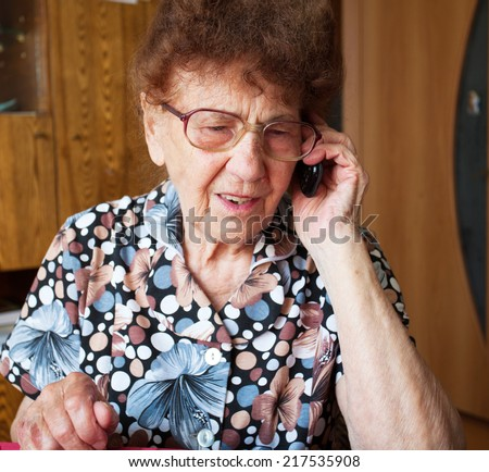 Old woman. Elderly female at home talking for mobile phone - stock photo