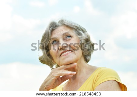 Old woman enjoying a walk on the nature