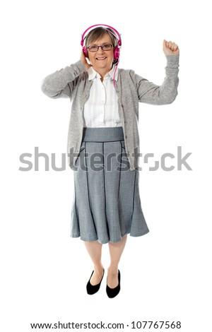 Old woman enjoying music through pink headphones against white background - stock photo
