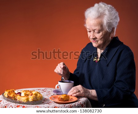 Old woman enjoying  tea cup with apple pie over orange background