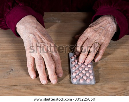 Old woman going to take the medicine at home - stock photo