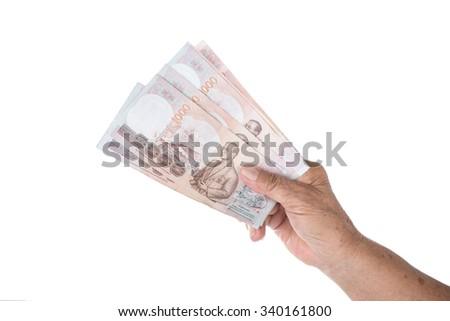 Old woman hand holding Thai money on white. - stock photo