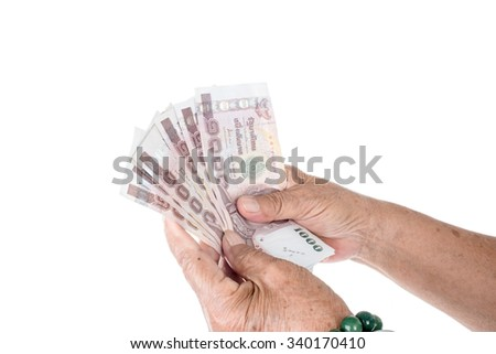Old woman hand holding Thai money on white.