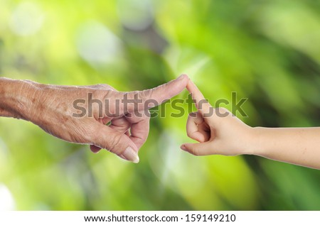 old woman hand touching a child's hand in green background