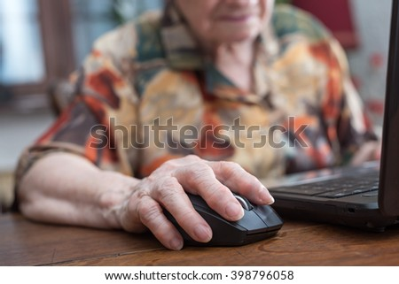 Old woman hand using the mouse of a computer - stock photo