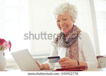 Old woman happy doing her shopping online using a credit card - stock photo