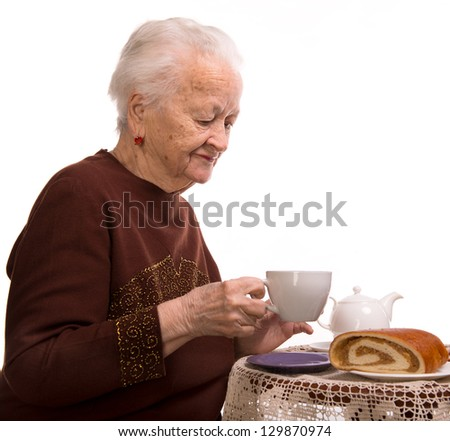 Old woman having breakfast on a white background