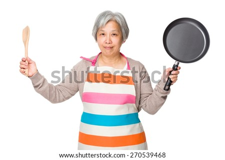 Old woman hold up with wooden ladle and fried pan - stock photo