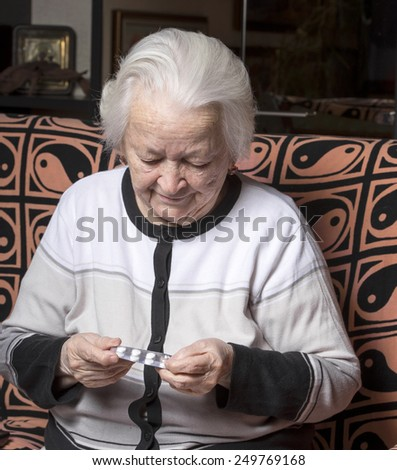 Old woman holding pills at home - stock photo