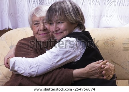 Old woman hugging her daughter - stock photo
