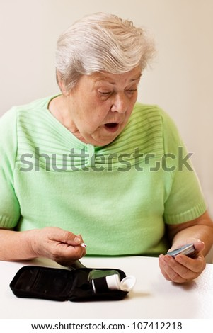 old woman in blood sugar measure is shocked by the values - stock photo