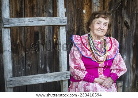 Old woman in ethnic red and white dress and necklace, outdoors in the village.  - stock photo
