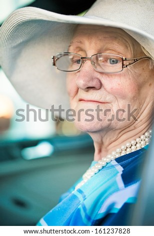old woman in glasses and a hat sitting in the car . - stock photo