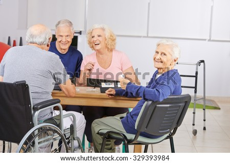Old woman in nursing home playing with laughing senior people - stock photo