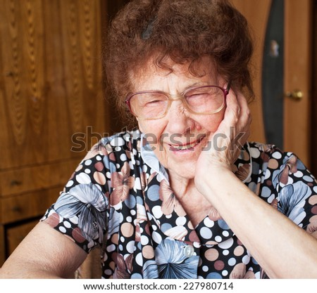 Old woman. Laughing elderly female at home - stock photo