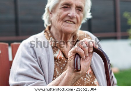 old woman leaning on her stick - stock photo