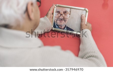 Old woman looking at her husband photo. Widow has nostalgia after a life together - stock photo