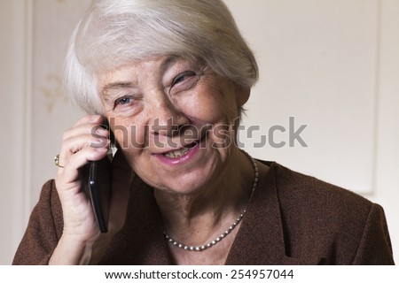 Old woman making a phone-call - stock photo
